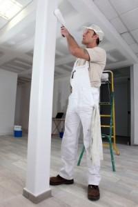 peintre peignant une poutre en bois