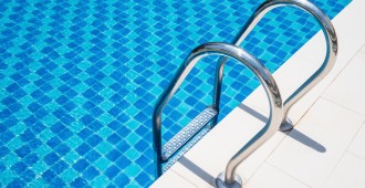 Closeup grab bar ladder in the blue swimming pool at the hotel 1