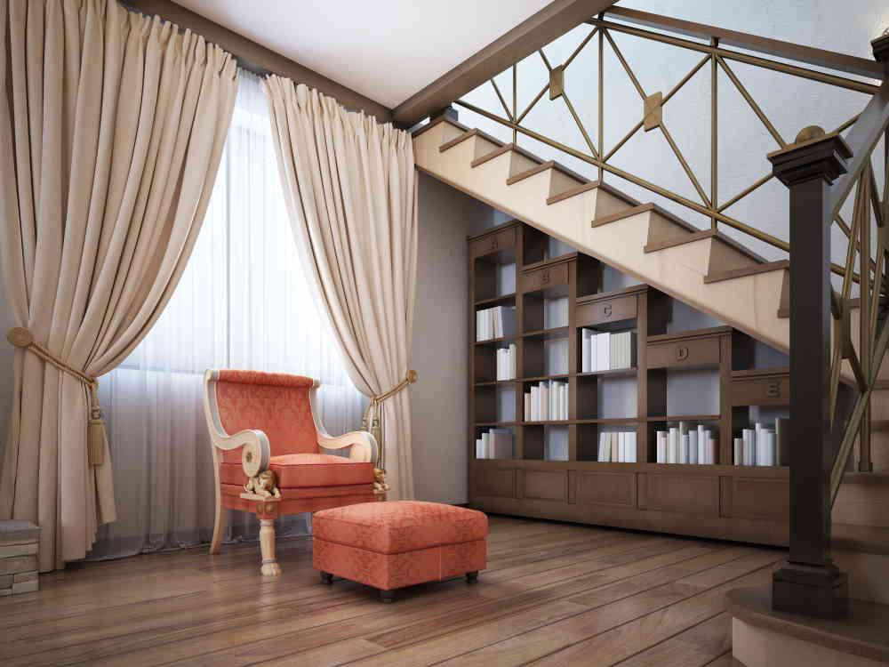 Coin lecture sous l'escalier avec un fauteuil et repose-pied